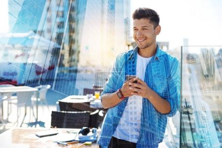 Cheerful man holding his phone and smiling