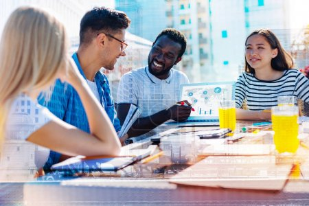 Happy afro-american man discussing work with his co-workers