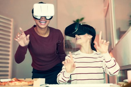 Two cheerful friends having fun with VR headsets
