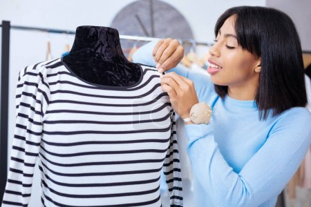 Careful tailor finishing stitches on the striped blouse and looking attentive