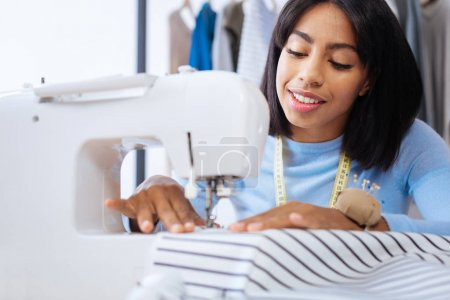 Attentive tailor smiling while using a modern convenient sewing machine