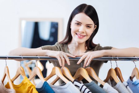 Cute young woman smiling while touching the clothes rail