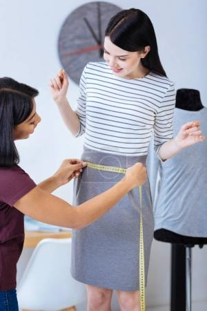 Professional tailor measuring the waist of a client and looking glad