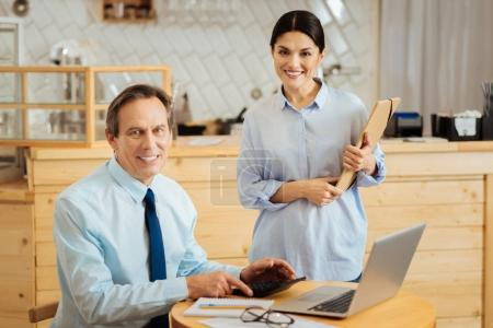 Pleasant satisfied man sitting and using the laptop.