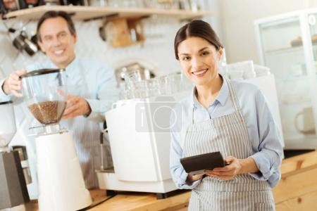 Pleasant cute woman standing and using the calculator.