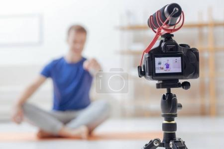 Confident blogger recording his new yoga lesson while being at home