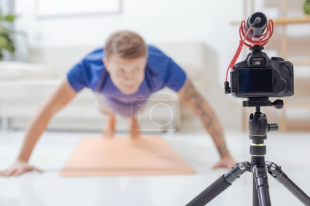 Young blogger looking at the camera while doing pushups