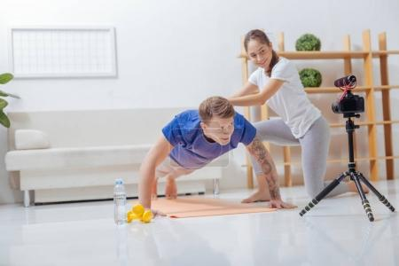 Cheerful instructor touching the back of her assistant while showing exercises