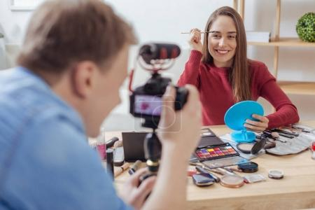 Happy fashion blogger testing cosmetics while her friend recording it