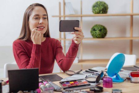 Photo pour Rouge à lèvres vif. Jolie jeune blogueur belle assis à la table et la mise sur le rouge à lèvres belle tout en regardant l'écran de son smartphone - image libre de droit