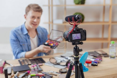 Photo pour Grande palette. Jeune calme attentionné blogger assis devant une caméra moderne et démontrant une nouvelle palette étonnante de l'ombre - image libre de droit