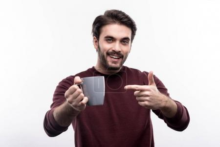 Cheerful young man pointing at the cup of coffee