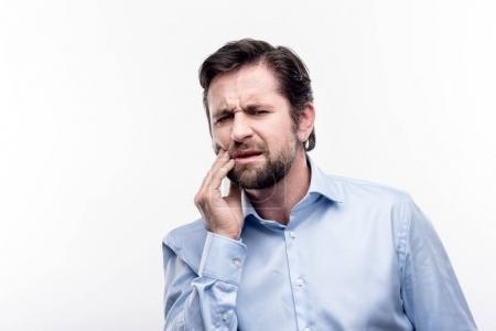Dark-haired middle-aged man suffering from toothache