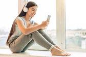 Pretty teenage girl listening to music on window sill