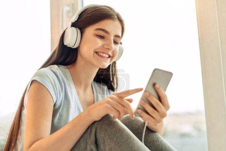 Cute teenage girl choosing music to play