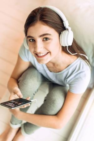 Top view of cute teenage girl listening to music