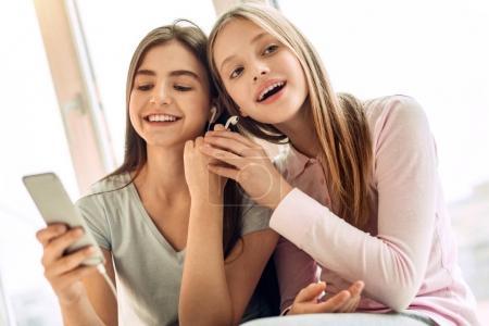 Sœurs adolescentes mignonnes partage une paire d'écouteurs