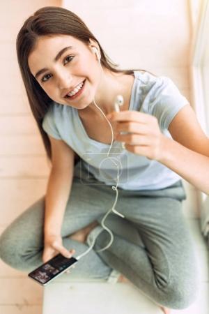 Top view of pleasant teenage girl offering one earphone