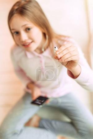 Cute teenage girl giving one earphone