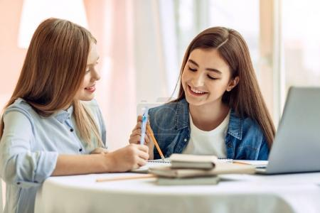 Pleasant girl helping her sister with home assignment