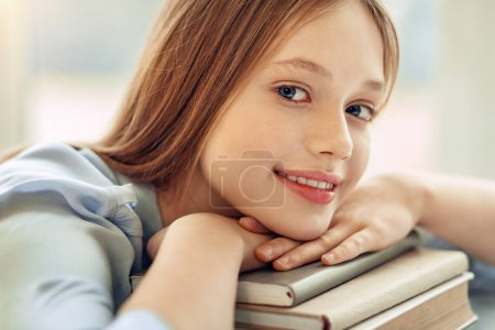 Close up of charming girl resting chin on books