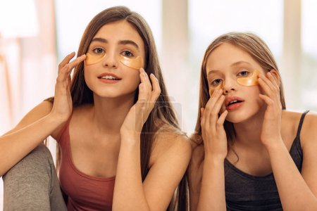 Photo pour Routine de soins de la peau. Belles filles adolescentes assis dans leur chambre et appliquer les correctifs sous les yeux, prenant bien soin de leur peau, tout en posant pour la caméra - image libre de droit