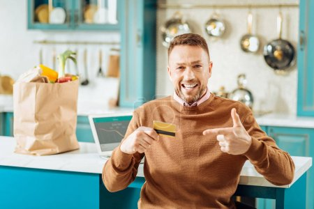 Happy nice man pointing at the credit card