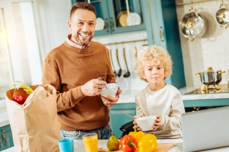 Positive joyful father and son eating breakfast