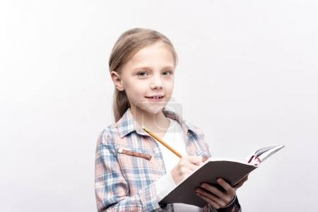 Charming little girl writing in a notebook