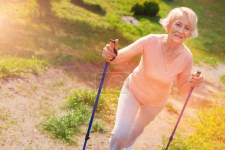 Optimistic elderly woman having a rest outdoors
