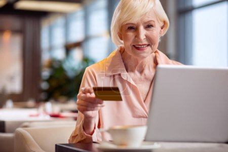 Positive mature woman using credit card