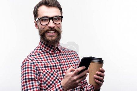 Photo pour Hip Man. Charmant jeune homme barbu en chemise à carreaux souriant à la caméra, tenant une tasse de café et envoyant un texto à quelqu'un tout en posant isolé sur un fond blanc - image libre de droit