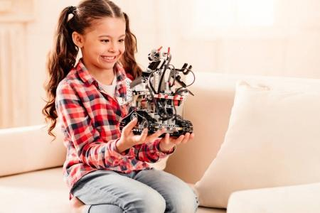 Adorable little girl getting excited over robotic machine