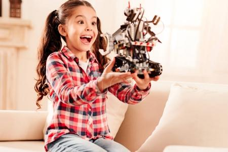 Excited preteen child getting emotional over robot toy