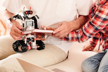 Close up of child and grandad playing with robotic machine
