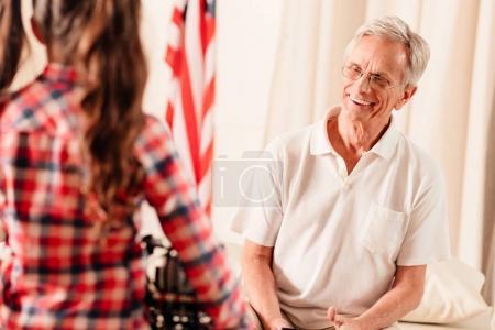 Cheerful retired gentleman listening to his granddaughter