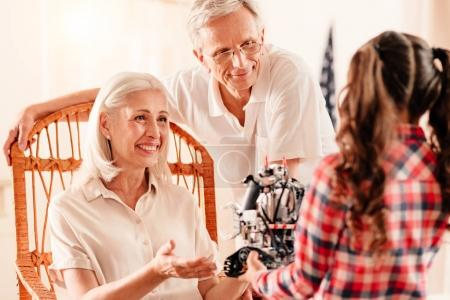 Loving grandparents listening to child talking about her robot toy