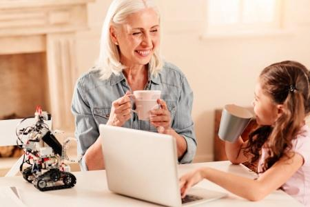 Extremely happy senior lady listening to her granddaughter