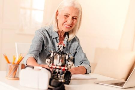 Elderly engineer examining newly constructed robot