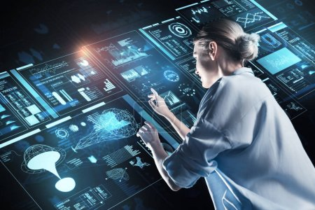 Photo for Looking interested. Clever experienced young programmer standing in front of a big futuristic device and touching the icons on it - Royalty Free Image