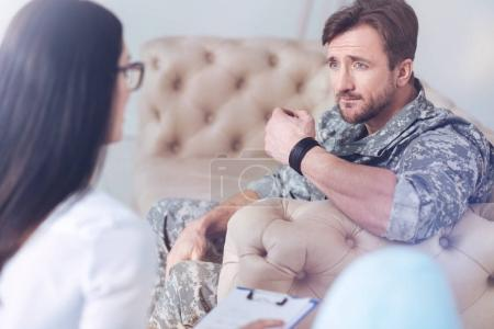 Millennial military servant listening to female psychotherapist