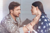 Military husband comforting anxious wife covered in USA flag