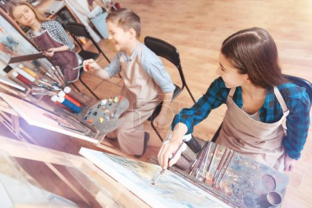 Funny children getting excited while painting