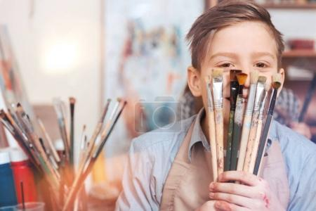 Adorable youngster hiding behind brushes for camera