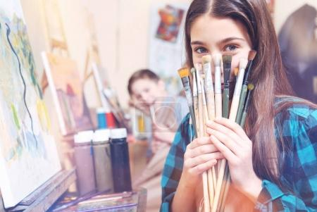 Pretty young lady showing bunch of old painting brushes