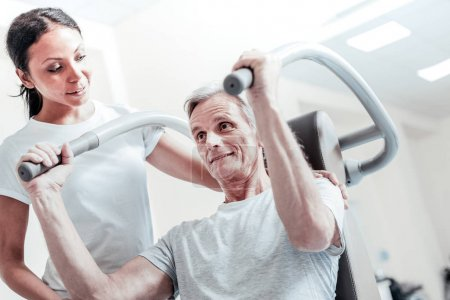 Joyful old man exercising with his female trainer