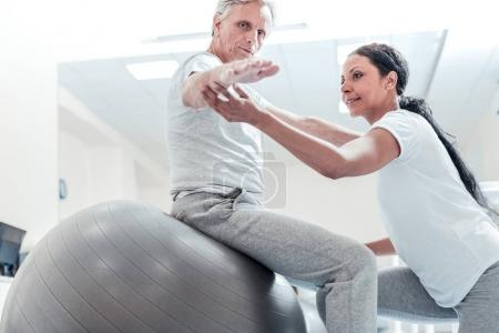 Concentrated trainer helping old man exercise