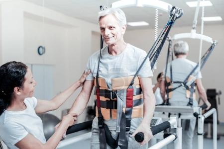 Alert aged man training in the gym with his trainer