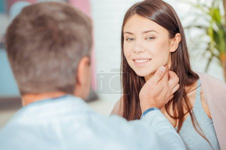Mature doctor talking to female patient