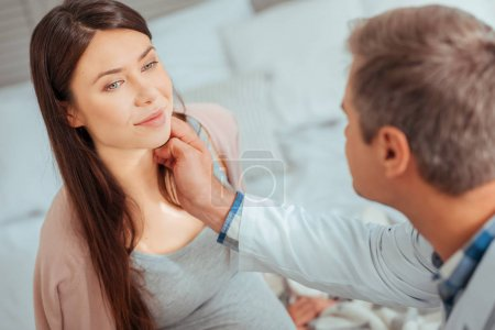 Male pediatrician checking lymph nodes of expectant mother